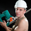 The builder in a protective helmet holds the professional puncher-hammer with a drill of the big diameter - Stock fotografie