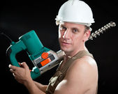 The builder in a protective helmet holds the professional puncher-hammer with a drill of the big diameter — Stock Photo