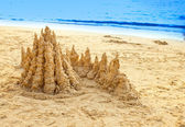 Sandy castle at the sea edge — Stock Photo