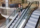 Young woman with backpack on the escalator — Stock Photo