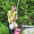 The boy, the teenager, pours water in a bucket from a well — Stock Photo