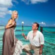 Man gives a rose to the woman on the turquoise sea background. — Stock Photo #8780651