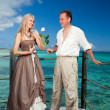 Man gives a rose to the woman on the turquoise sea background — Stock Photo #8780671