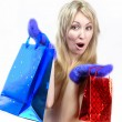 Stock Photo: Young womin bright mittens with elegant packages rejoices