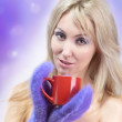 Portrait of the young blonde in fluffy mittens and with a mug — Stock Photo