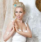 Glückliche Braut versucht auf ein Hochzeitskleid — Stockfoto