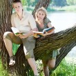 Young guy and the girl prepare for lessons, examination in spring park — Stock Photo #9247643