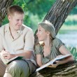 Young guy and the girl with textbooks on the bank of lake — Stock Photo #9247648
