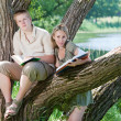 Young guy and the girl with textbooks on the bank of lake — Stock Photo #9247652