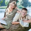 Young guy and the girl with textbooks on the bank of lake — Stock Photo #9247656