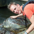 The man strokes an armor of a large turtle — Stock Photo #9247713