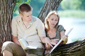 Young guy and the girl prepare for lessons, examination in spring park — Stock Photo