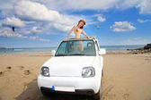 The young beautiful woman in the car on seacoast. — Stock Photo