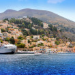 Foto Stock: Boats and houses on symi island, Greece