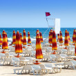 The closed beach umbrellas and red flag -swimming is forbidden — Stock Photo