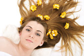 Portrait of beautiful spa woman with flower in hair. — Stock Photo