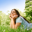 Beautiful young woman relaxing in the park at sunny spring day - Stockfoto