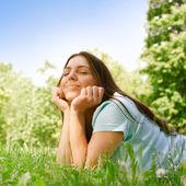 Mulher jovem e bonita relaxante no parque no dia ensolarado de primavera — Fotografia Stock