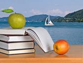 Knihy a jablka na stole — Stock fotografie