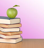 Green apple on books on desk — Stockfoto