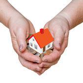 Ręce z prezentem w pieniędzy i domu — Zdjęcie stockowe