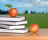 Books and red apples on desk — Stock Photo
