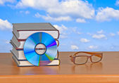 DVD, eyeglasses, and books — Foto de Stock
