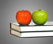 Röda och gröna äpplen på böcker på skrivbord — Stockfoto