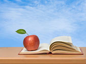 Red apple and book on desk — Stock Photo
