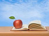 Rött äpple och bok på skrivbord — Stockfoto