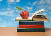 Red apple and books on desk — Stockfoto