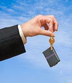 Zbliżenie dłoni trzymając klucz na tle nieba — Zdjęcie stockowe