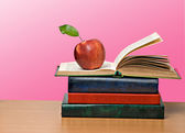 Red apple and open book — Stock Photo