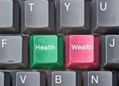 Keyboard with keys for health and wealth — Stock Photo