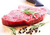 Raw meat with rosemary — Stock Photo