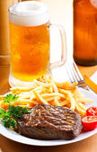 Grilled steak with mug of beer — Stock Photo