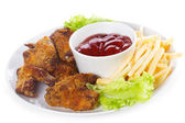 Chicken wings with sauce and fries — Stock Photo