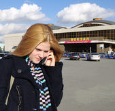 Girl speaks phone at background of station.Chelyabinsk.Russia. — Stock Photo