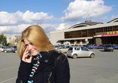 Girl speaks over telephone on railway station back — Stock Photo