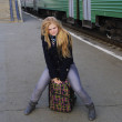 Girl is sitting on suitcase on background of train — Stock Photo