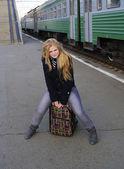 Chica está sentada en la maleta en el fondo del tren — Foto de Stock