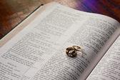 Wedding rings lying on Bible — Stock Photo