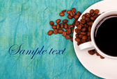 Coffe in cup with coffee beans in and around the soucer — Stock Photo
