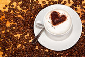 Cacao heart in white frothed coffee — Stock Photo
