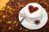 Star aniseed and cacao heart in coffee — Stock Photo