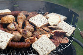 Barbecue with delicious grilled meat on grill — Stock Photo