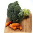 Brocolli and carrots on the cutting board on the white background — Stock Photo