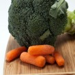 Stock Photo: Brocolli and carrots on cutting board on white background