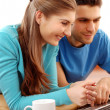 Smiling young couple using laptop at home — Stock Photo