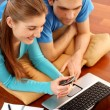 Smiling young couple using laptop at home — Stock Photo #9592885